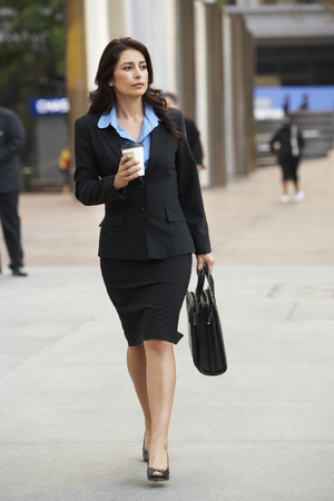 Businesswoman Walking Along Street Holding Takeaway Coffee photo