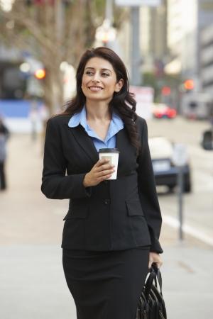 takeaway: Businesswoman Walking Along Street Holding Takeaway Coffee