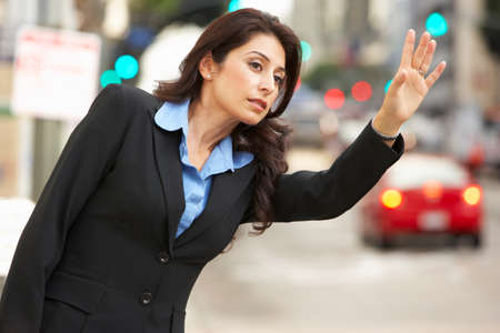 hailing: Businesswoman Hailing Taxi In Busy Street