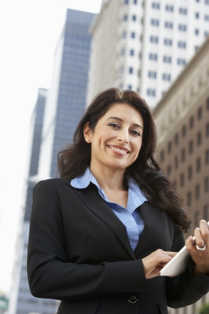 Businesswoman Working On Tablet Computer Outside Office photo