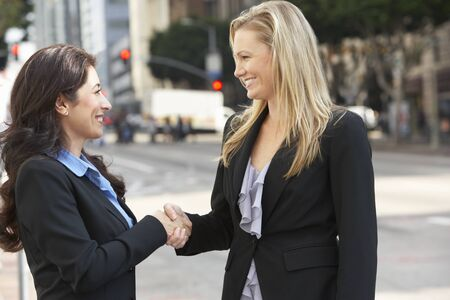 Two Businesswomen Shaking Hands Outside Office photo