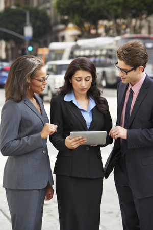 Businessman And Businesswomen Using Digital Tablet Outside photo
