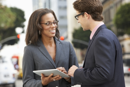 discussing: Businessman And Businesswoman Using Digital Tablet Outside Stock Photo