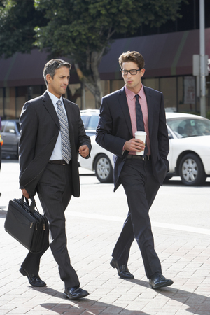 talking businessman: Two Businessman Chatting Whilst Crossing Street Stock Photo