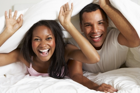 waking up: Couple Relaxing In Bed Hiding Under Duvet Stock Photo