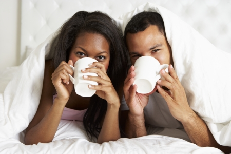 Couple Relaxing In Bed With Hot Drink photo