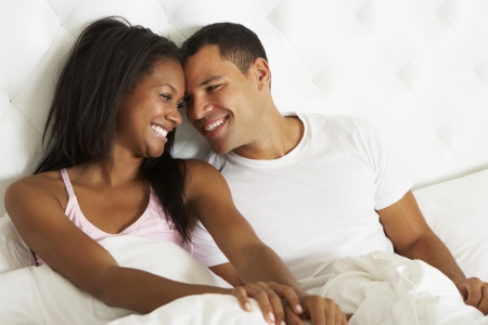 Couple Relaxing In Bed Wearing Pajamas photo