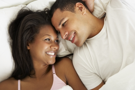 romance bed: Couple Relaxing In Bed Wearing Pajamas
