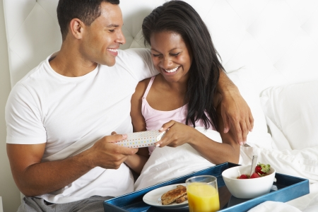 day bed: Man Bringing Woman Breakfast In Bed On Celebration Day Stock Photo
