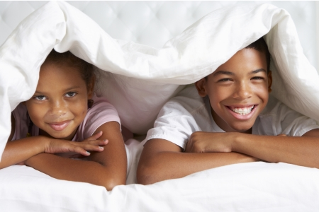 girl lying: Two Children Hiding Under Duvet In Bed