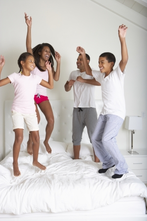 bouncing: Family Jumping On Bed Together Stock Photo