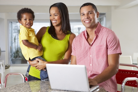Family Using Laptop In Kitchen Together photo