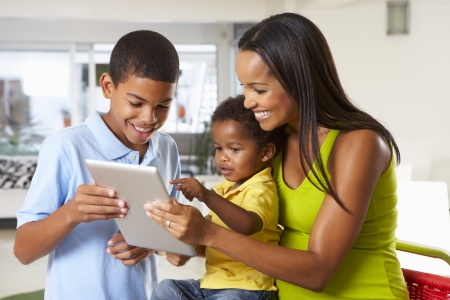 Mother And Children Using Digital Tablet In Kitchen Together photo