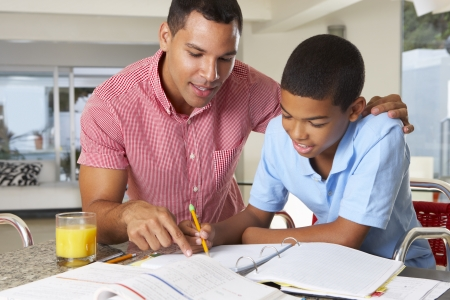 father and child: Father Helping Son With Homework In Kitchen