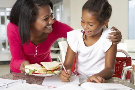 niños estudiando: Madre trae Sandwich Hija Mientras estudia Foto de archivo