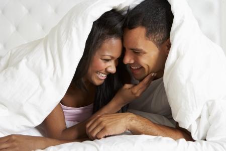 pareja abrazada: Pares que se relajan en la cama que oculta bajo Edred�n Foto de archivo