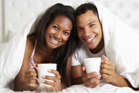 pareja abrazada: Pares que se relajan en la cama con la bebida caliente