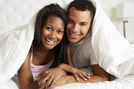 Couple Relaxing In Bed Hiding Under Duvet photo