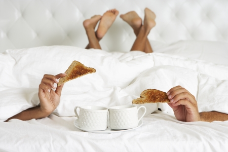 bedding indoors: Couple Hiding Under Duvet Enjoying Breakfast In Bed