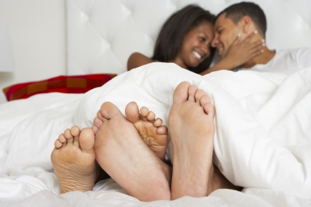 couple au lit: Couple de d�tente dans son lit portant Pyjamas