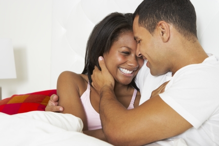 african american couple: Couple Relaxing In Bed Wearing Pajamas