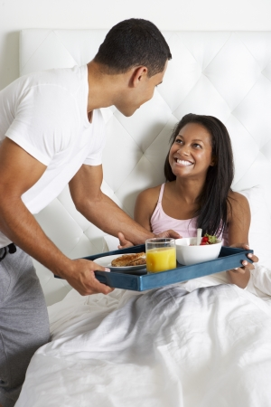 Man Bringing Woman Breakfast In Bed On Tray photo