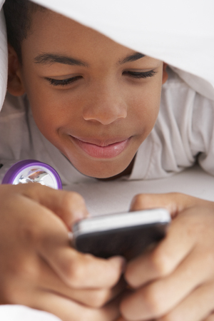 Boy Using Mobile Phone Under Duvet photo