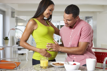 Pregnant Woman And Husband Having Breakfast In Kitchen photo
