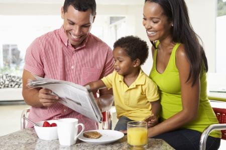 parent and child: Familia que tiene el desayuno en cocina Juntos Foto de archivo
