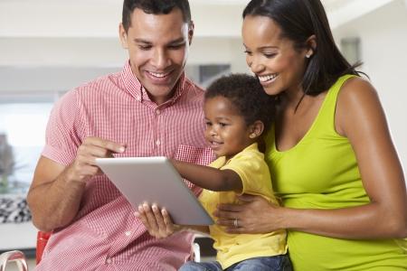 old black man: Family Using Digital Tablet In Kitchen Together