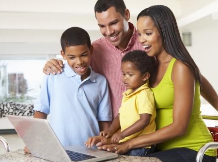 old black man: Family Using Laptop In Kitchen Together