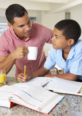 Father Helping Son With Homework In Kitchen photo