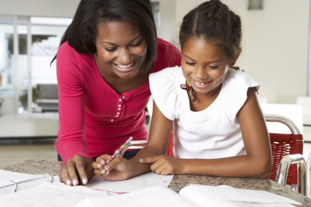 homework: Mother Helping Daughter With Homework In Kitchen Stock Photo