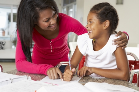 teaching children: Mother Helping Daughter With Homework In Kitchen Stock Photo