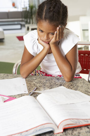 Fed Up Girl Doing Homework In Kitchen photo