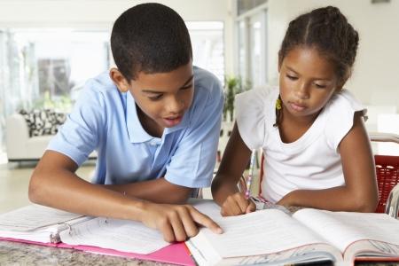 台所で一緒に宿題をやっている 2 人の子供 写真素材