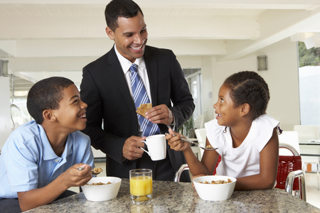 people eating: Father Having Breakfast With Children Before Work