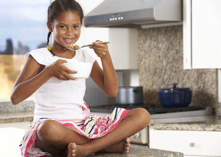 Girl In Kitchen Eating Bowl Of Breakfast Cereal photo