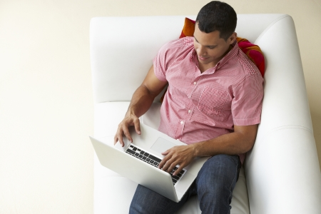 Overhead View Of Man Relaxing On Sofa Using Laptop photo