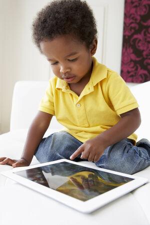 niños africanos: Muchacho feliz en el sofá que juega con la tablilla digital