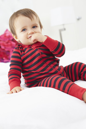 Toddler Sitting On Bed Wearing Pajamas photo