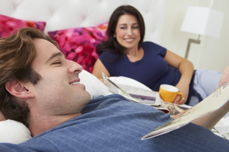 Couple Relaxing In Bed With Coffee And Newspaper photo