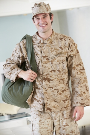 Male Soldier With Kit Bag Home For Leave Stock Photo