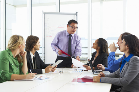 Businessman Conducting Meeting In Boardroom photo