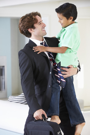 welcome home: Son Greets Father On Return From Work Stock Photo