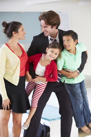 arriving: Family Greeting Father On Return From Work Stock Photo