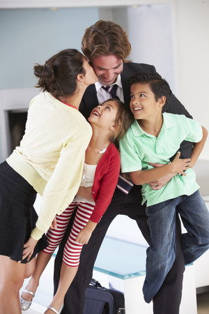 Family Greeting Father On Return From Work photo