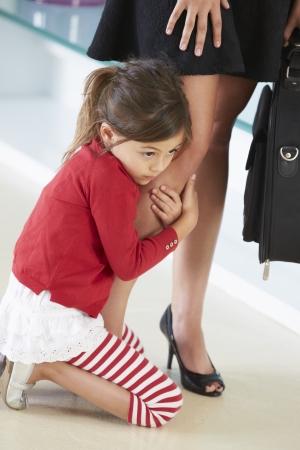 働く母親の足にしがみつくの娘