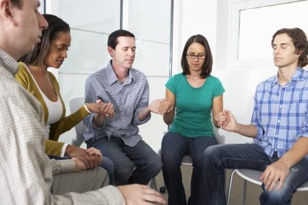 praying together: Bible Group Praying Together Stock Photo