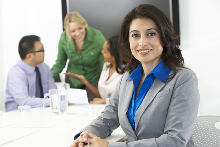 on the foreground: Portrait Of Businesswoman In Boardroom With Colleagues